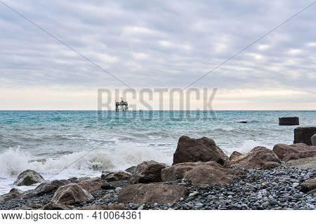 Winter Beach With Seascape And A Rickety Structure On The Stilts Of An Mariculture Farm In The Dista