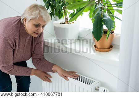 Senior Woman Trying To Keep Warm By Warming Hands On The Heating Radiator In Winter Time