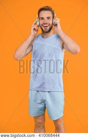 Man Handsome Unshaven Sportsman Listening Music Headphones Gadget. Wireless Headphones For Sport. Mo