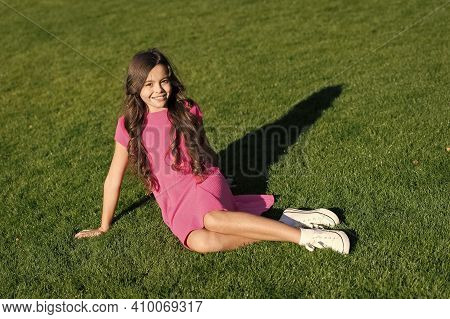 Small And Beautiful. Happy Small Girl Sit On Green Grass. Small Child Wear Summer Dress. Adorable Sm