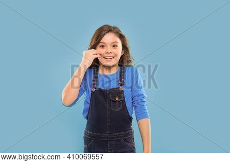 Advantages Of The Young Skin. Happy Little Girl Touching Her Smooth Baby Skin On Blue Background. Sm