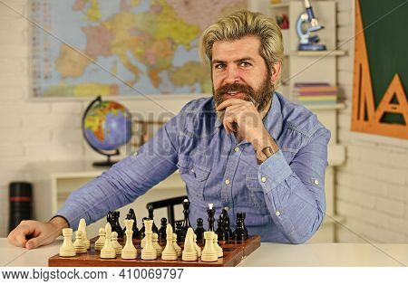 Brain Works Like A Muscle. Concentrated Man Developing Chess Strategy. Playing Board Game With Frien