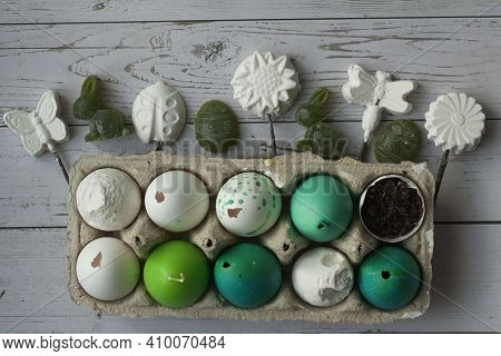 Green And White Easter Eggs In Egg Carton. Candle Egg, Gypsum Egg, Poultry Egg, Ground On Wooden Bac