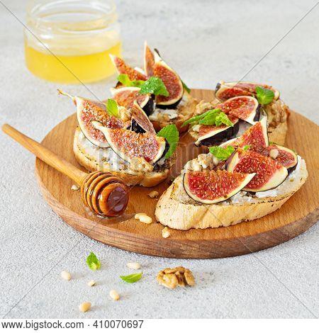 Crispy Bruschetta (toast) With Soft Ricotta, Ripe Figs, Walnuts And Pine Nuts, Mint And Honey On A L