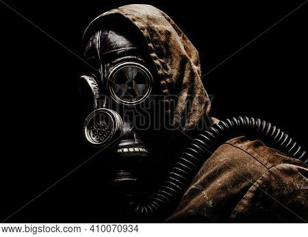 Stalker Warrior In Protective Soviet Gas Mask Standing On Dark Background With Radiation Sign.
