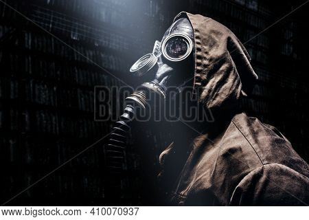 Stalker Warrior In Protective Soviet Gas Mask Standing In Tunnels And Looking Up At Light Beam.