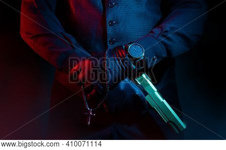 Photo Of A Male Mafia Criminal Killer In Suit And Leather Gloves Holding A Gun With Cross On Black B