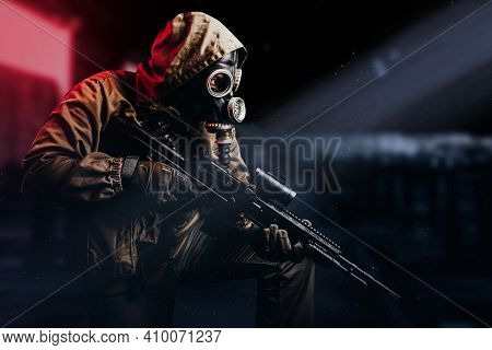 Photo Of A Post Apocalyptic Stalker Soldier In Gas Mask And Hood Jacket Holding Rifle And Sitting On