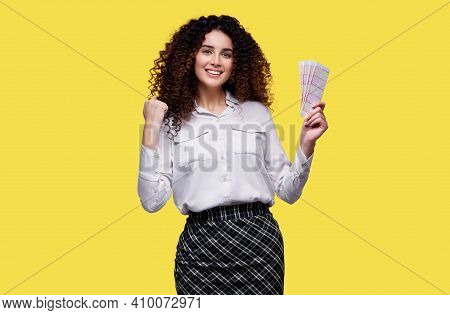 Young Woman Won The Lottery. Happy Female Holding Lottery Ticket On Yellow Isolated Background.