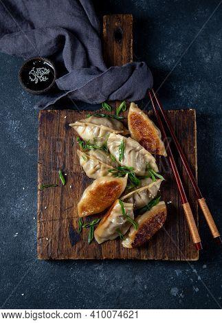 Asian Dumplings Gyoza Potstickers On Old Wooden Board. Top View, Copy Space