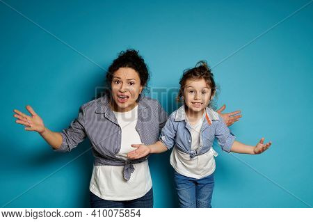 A Woman And Her Little Daughter, Dressed Alike, Look At The Camera With Open Arms, Expressing Disple