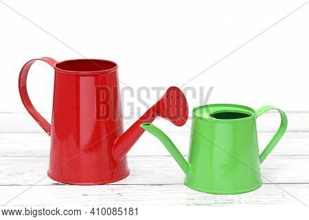 Green And Red Watering Can On White Wooden Table