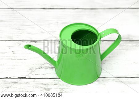 Green Watering Can On White Wooden Table