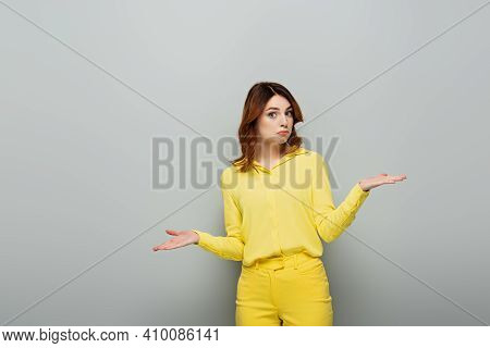 Discouraged Woman In Yellow Clothes Showing Shrug Gesture And Looking At Camera On Grey.