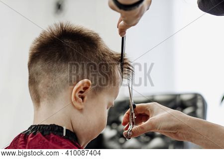 Little Boy Gets His Hair Cut With A Pair Of Barber Scissors. Close-up Of Woman Hands Grooming Kid Bo