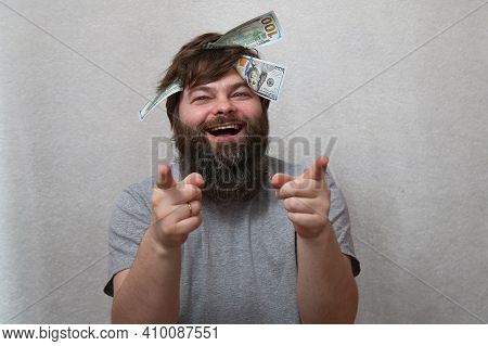 A Happy Bearded Man With Cash Bills In His Mop Of Hair. A Gesture With The Index Fingers. Concept: B