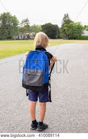 Little Blond Child Carrying Blue Backpack, Walking To School. Back To School Concept. Child Near Sch