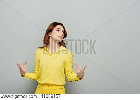 Arrogant Woman Pointing With Fingers At Herself While Looking Away On Grey.