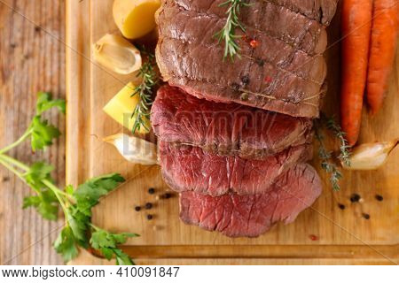 roasted beef sliced with sauce and potatoes