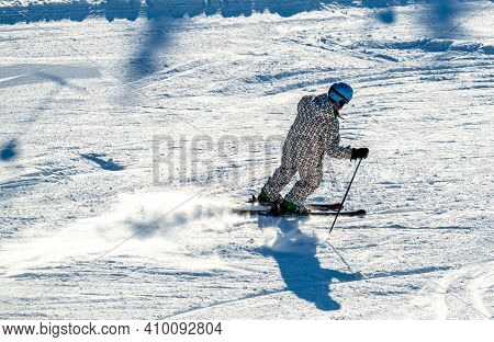 Close Up Of A Downhill Skier Speeding Down A Mountain With A Trail Of Snow.