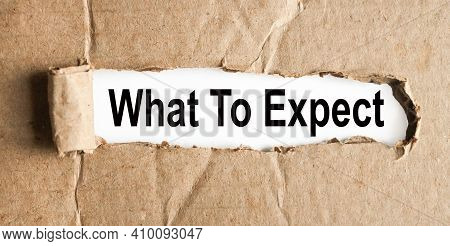 What To Expect. Text On White Paper Over Torn Paper Background.