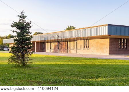 School Building And Schoolyard On A Sunny Day. Back To School Or Summer Break Concept.