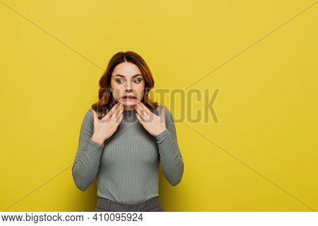 Affected Woman Grimacing While Holding Hands Near Chin On Yellow.