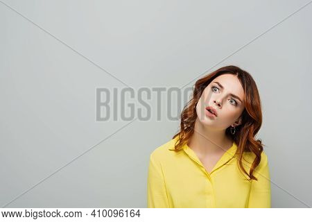 Amazed Woman In Yellow Blouse Looking Away Isolated On Grey.