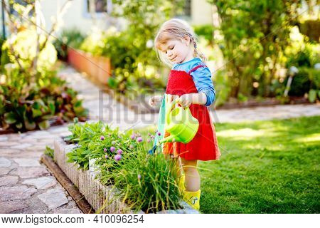 Beautiful Little Toddler Girl In Yellow Rubber Boots And Colorful Dress Watering Spring Flowers With