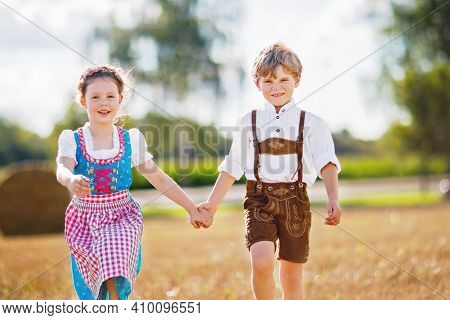 Two Kids In Traditional Bavarian Costumes In Wheat Field. German Children Sitting On Hay Bale During