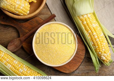 Cornmeal In Bowl And Fresh Cobs On Wooden Table, Flat Lay
