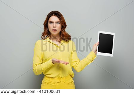 Discouraged Woman Pointing At Digital Tablet With Blank Screen On Grey.