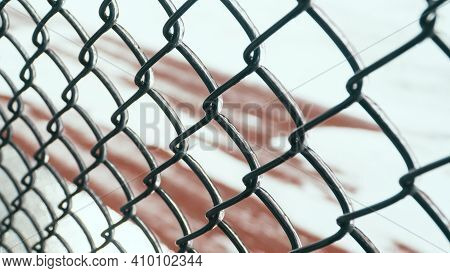 Metal Chain-link Fence With Ice On It And A Snowy Ground In The Background.