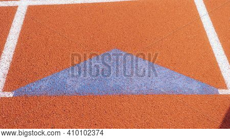Bright Blue Relay Exchange Triangle On Orange Running Track During A Sunny Day.