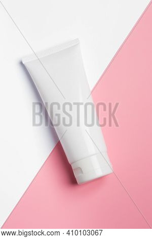 White Plastic Tube With Cream For Face, Hands And Body, On Light Pink Paper. Sun Protection Lotion,
