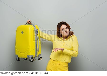 Discouraged Woman Pointing At Yellow Suitcase While Looking At Camera On Grey.