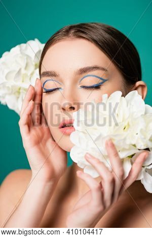 Charming Woman With Blue Eyeliner On Closed Eyes Posing With White Peonies Isolated On Green