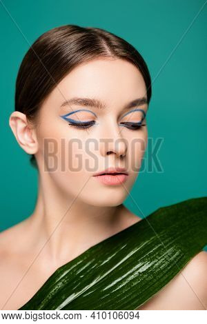 Young Sensual Woman With Blue Eyeliner Near Wet Leaf Isolated On Green
