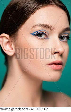 Close Up Portrait Of Pretty Young Woman With Blue Eyeliner Isolated On Green