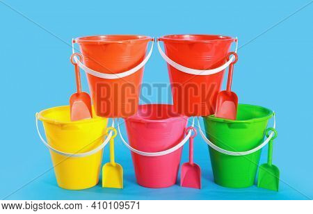 Sand pail bucket beach toys stacked in a rows with shovels