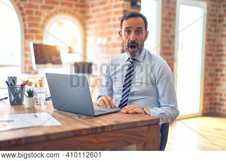 Middle age handsome businessman wearing tie sitting using laptop at the office afraid and shocked with surprise expression, fear and excited face.