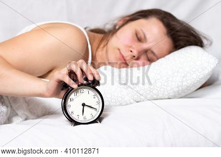 Girl Wakes Up In The Morning With Alarm Clock. Young Woman Lying In Bed In The Morning. She Is Wakin