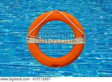 Safety Equipment, Life Buoy Or Rescue Buoy  On Swimming Pool  With Sunny Reflections
