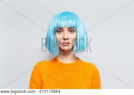 Studio Portrait Of Pretty Young Girl With Blue Bob Hairstyle In Orange Sweater On White Background.