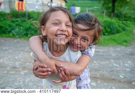 Lomnicka, Slovakia. 05-16-2018. Gypsy Smiling Girls Living In Misery And Poverty In A Abandoned Roma