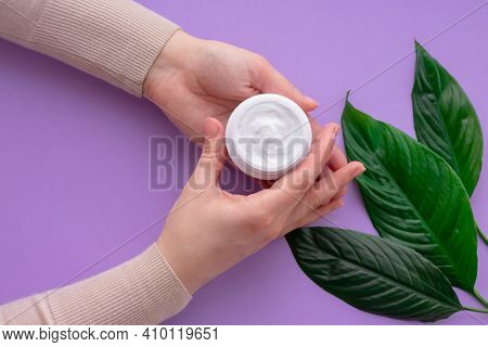 Young Girls Hand Nearby White Soft Cream In Jar With Green Leaves.concept Of Eco Cosmetic. Girl Is H