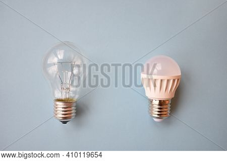 Comparing Filament And Fluorescent Lightbulbs On Blue Background. Old And New Eco Friendly Lightbulb