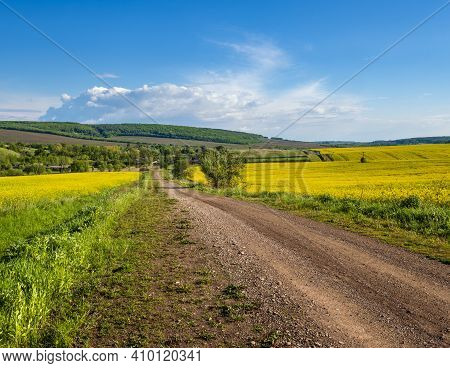 Spring Countryside View With Dirty Road, Rapeseed Yellow Blooming Fields, Village, Hills. Ukraine, L
