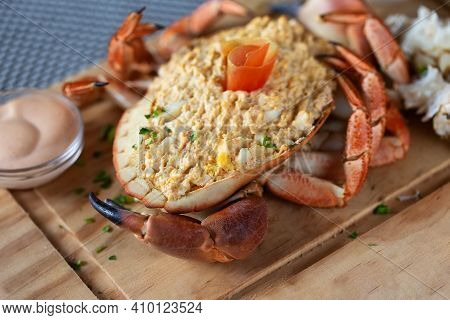 Closeup Of A Crab Shell Filled With A Mixture Of Egg, Mayonnaise And Crab Meat On A Wooden Board.