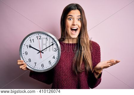 Young beautiful girl doing countdown holding big clock over isolated pink background very happy and excited, winner expression celebrating victory screaming with big smile and raised hands